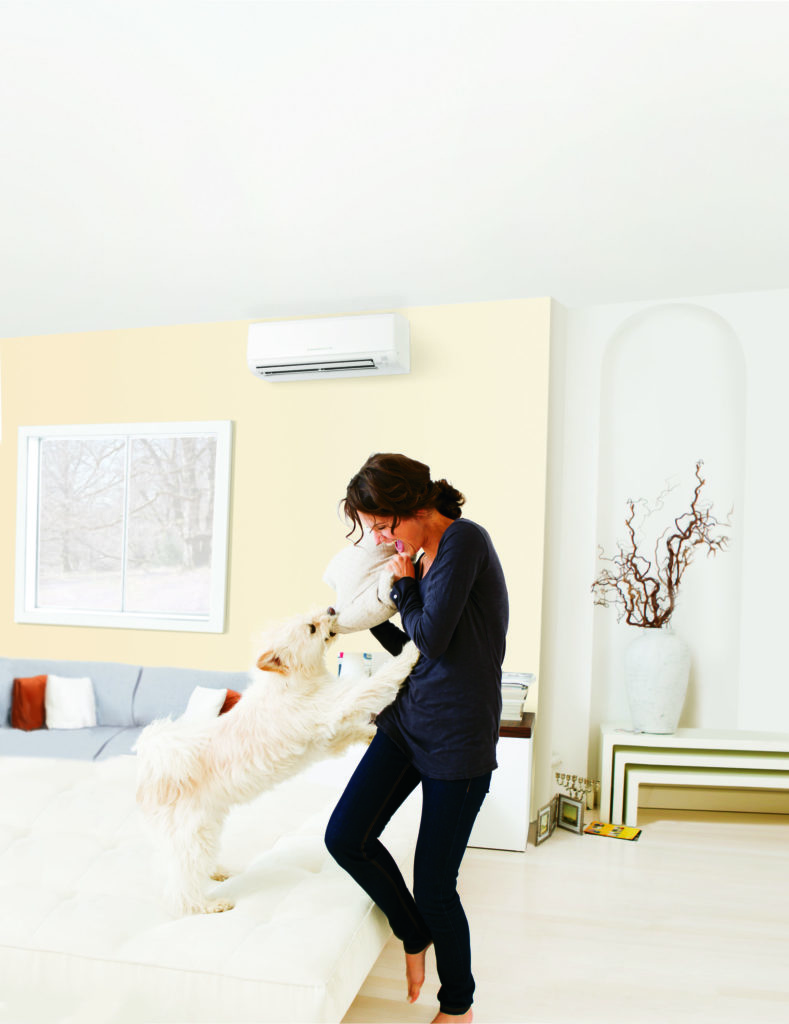 a woman plays with her dog in front of a mitsubishi ductless mini-split hvac system