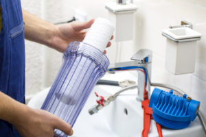 a man installs a water filter in charleton ma | plumbing and hvac in charlton ma