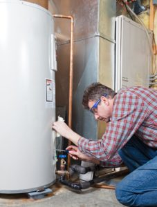 webster ma plumber working on a water heater repair in webster